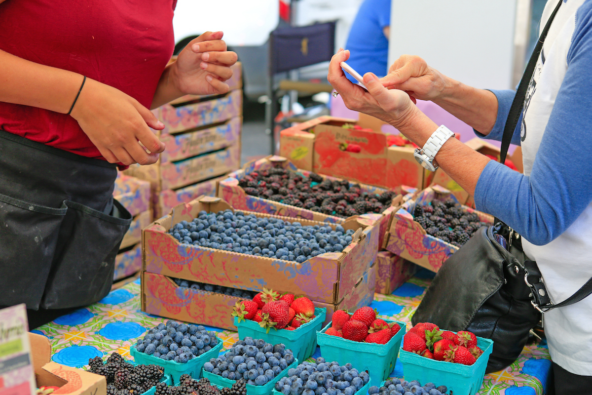 Fresh Baskets of Organically grown strawberries blackberries and blueberries for sale at the downtown farmers' market.