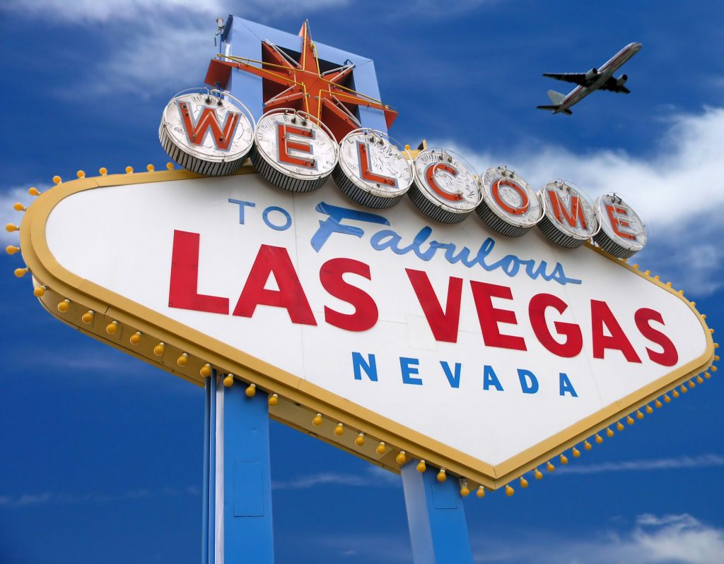 welcome to las vegas sign with plane flying overhead