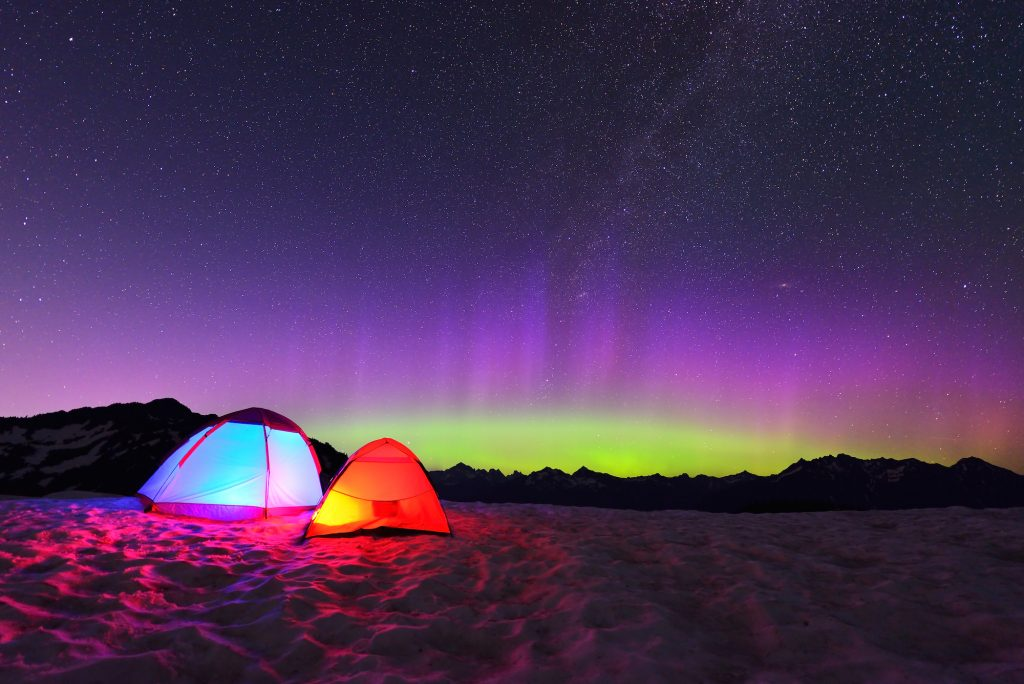 Aurora Borealis And Tents On Snow Mountain
