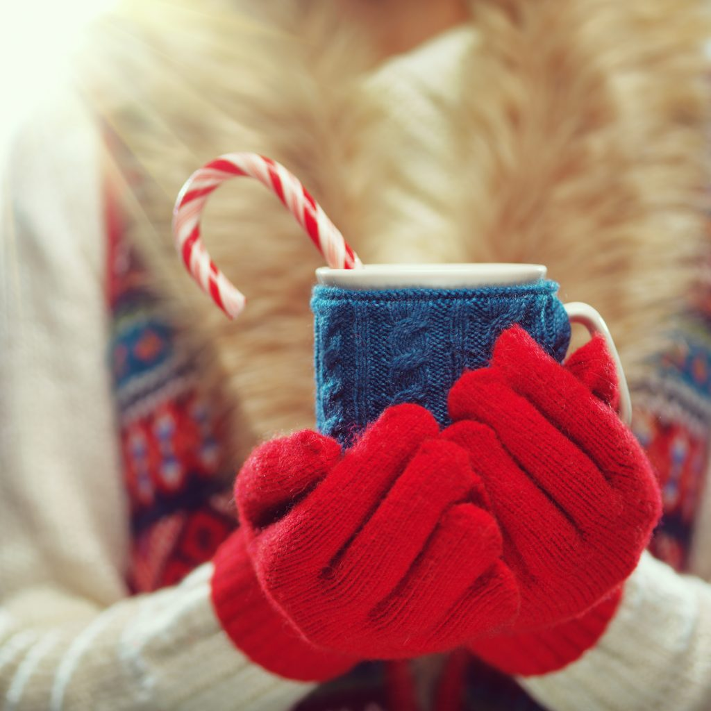 Woman with mittens holding mug of hot cocoa