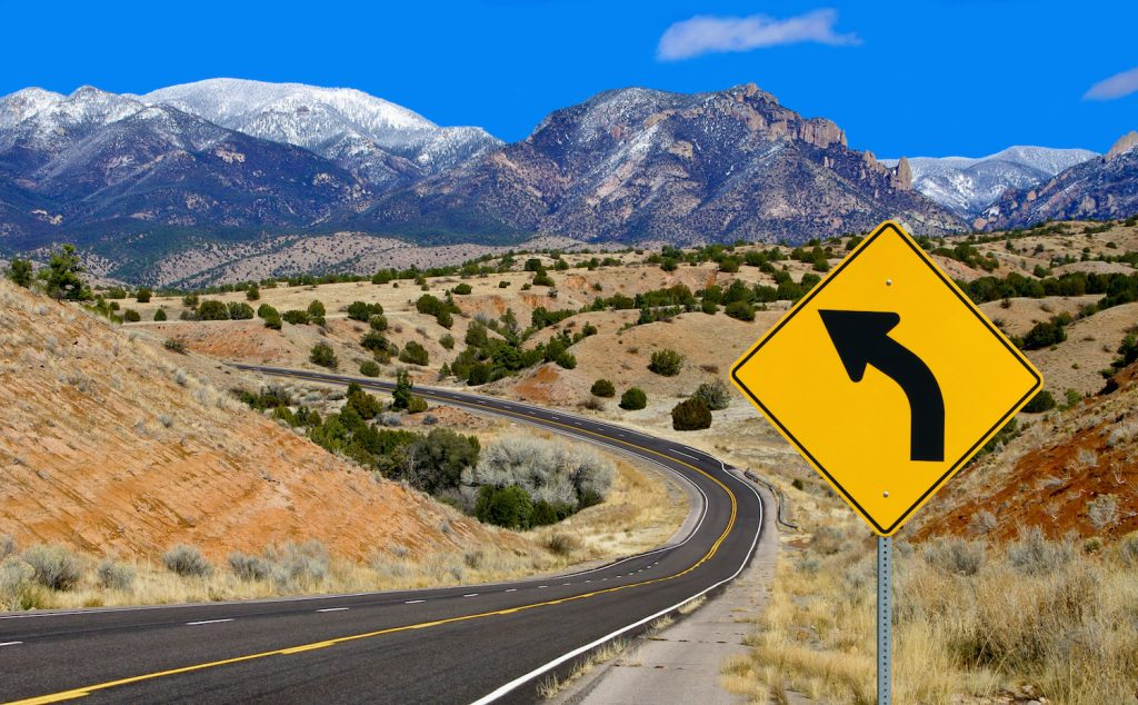A road sign alerts motorists to a curving mountain road in northern New Mexico.