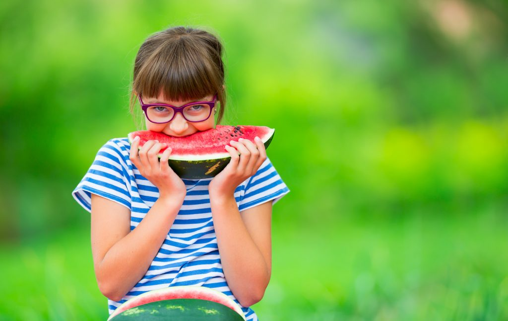 Child eating watermelon. Kids eat fruits in the garden. Pre teen girl in the garden holding a slice of water melon. happy girl kid eating watermelon.