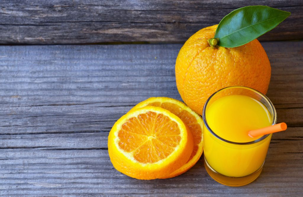 glass of fresh orange juice with a straw and fresh orange slices on a wooden background