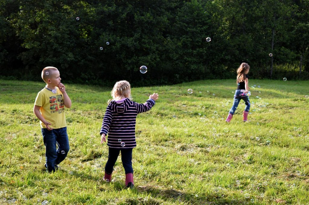 three kids in an open field playing with bubbles