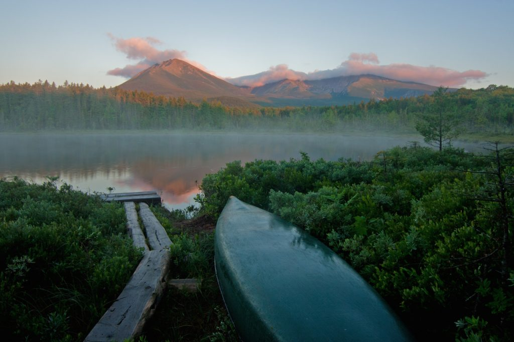 Canoe and trees on a lake in Maine. Mount Katahdin sunrise in the background.