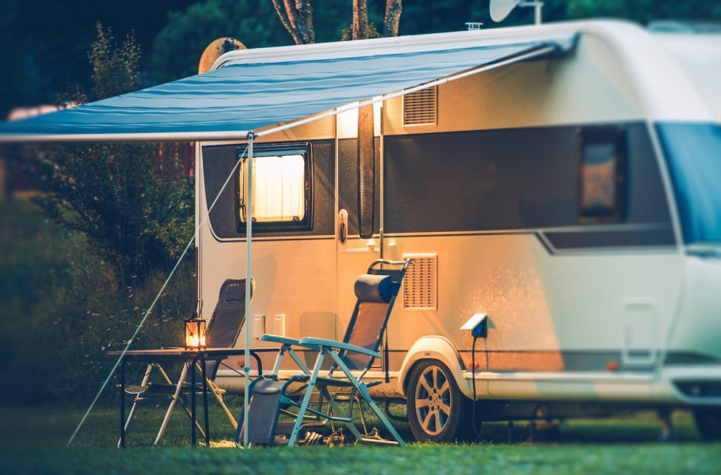 Travel Trailer Caravaning. An RV camper with an awning opened up on the outside