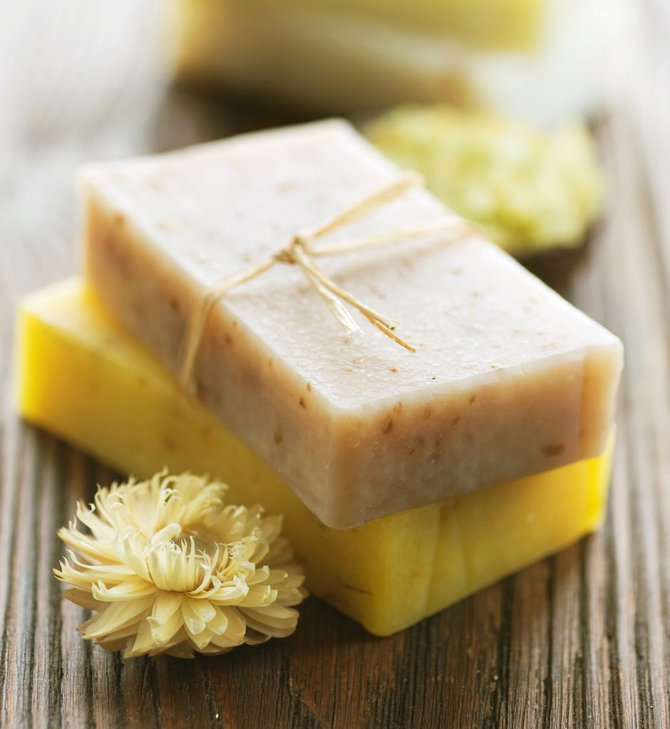 two bars of yellow handmade soap piled on eachother next to flowers