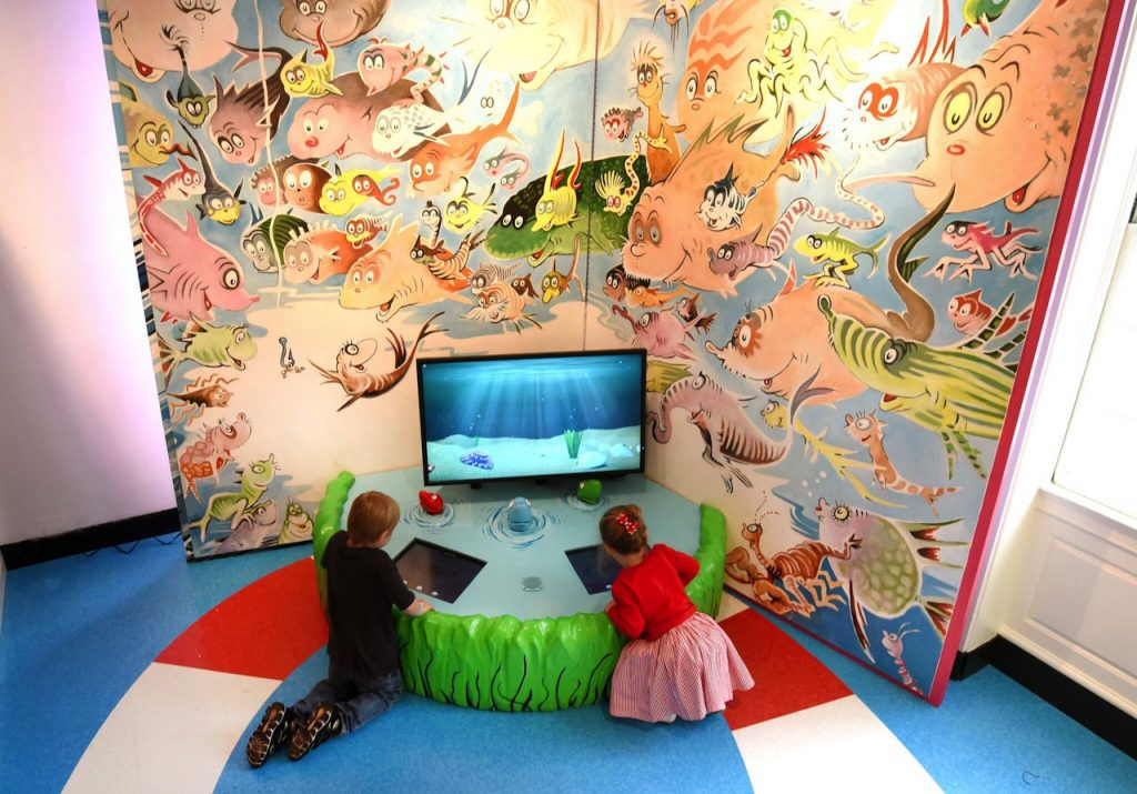 young boy and young girl playing on an interactive dr. seuss game in the Amazing World of Dr. Seuss Museum