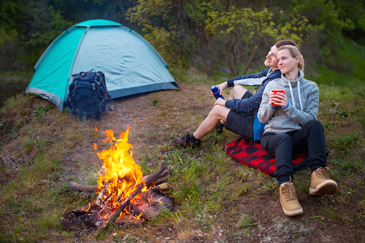 Young happy couple sitting and smile next to the campfire