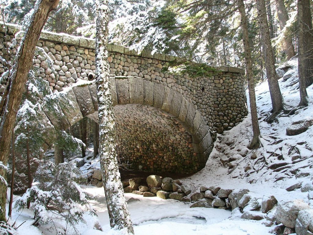 Acadia National Park bridge during winter with snow on it, frozen creek underneath