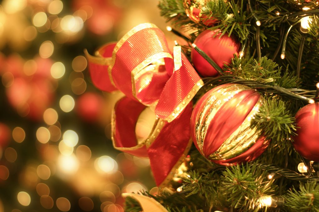 Red and gold ornaments on a christmas tree with lights