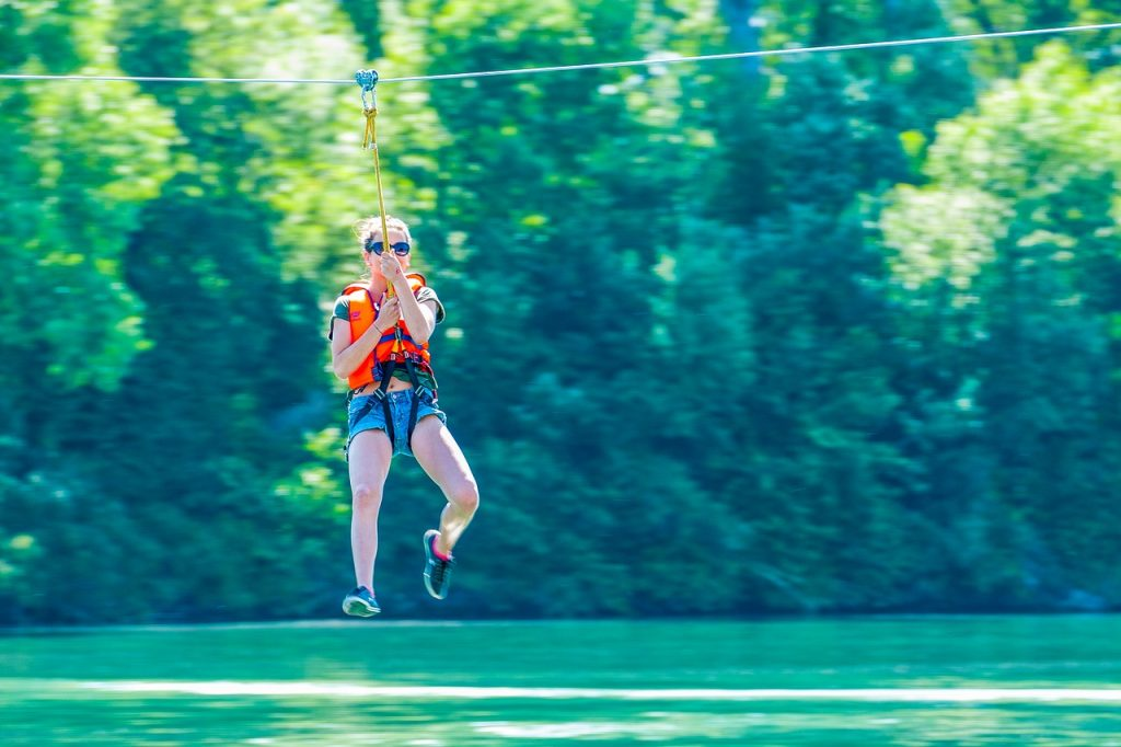 young girl zip lining over clear water, with large trees in the background