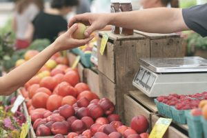 Exchange of hands at an outdoor Farmer's Market. Someone is purchasing fruit
