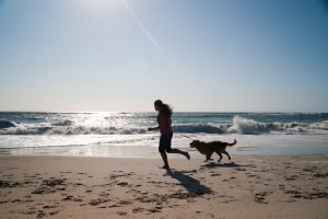 Girl and her dog playing on beach