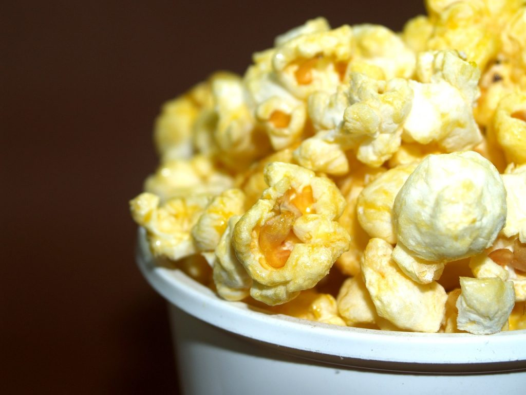 buttery popcorn upclose in a white bucket, with a brown background