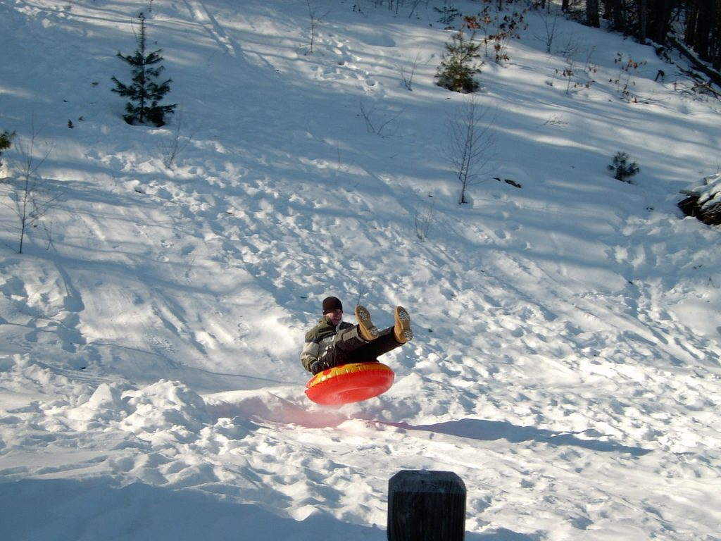 man snowtubing down a hill in a red tube