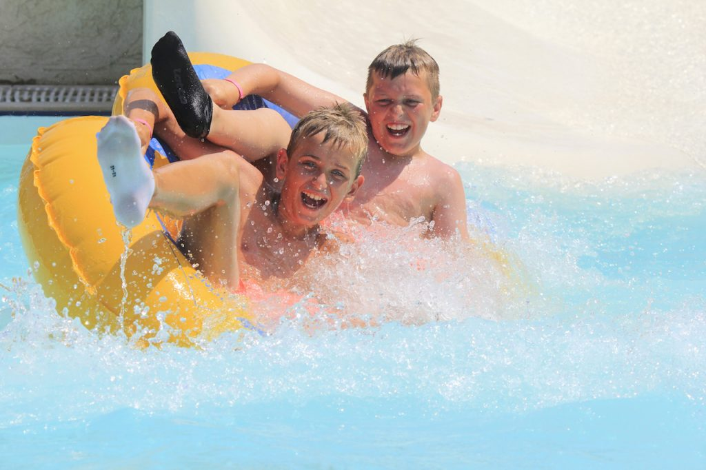 two young boys having fun in a waterpark, riding on an inner tube slide