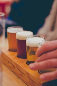 Close up of a mans handing grabbing a mini beer from a flight of beers