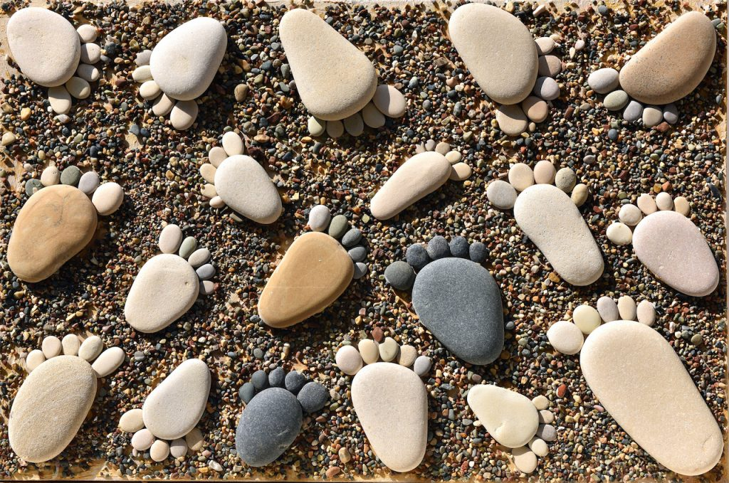 Pebble stones arranged like footprints on the beach