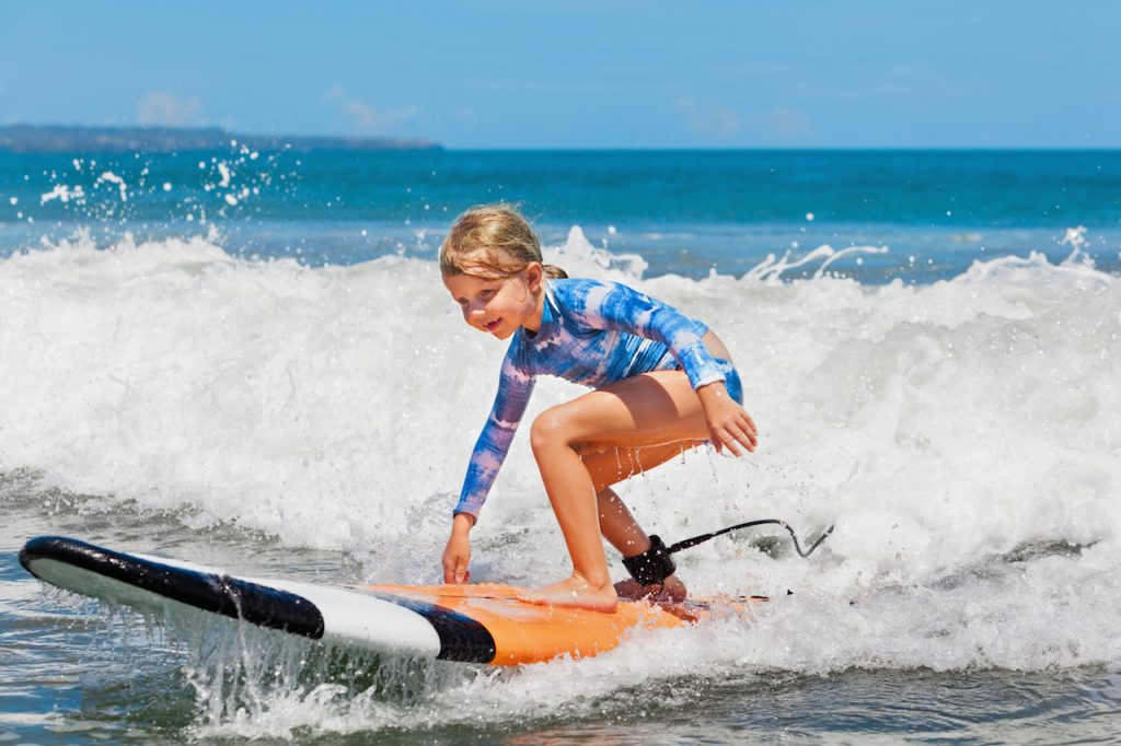 young surfer ride on surfboard with fun on sea waves. Active family lifestyle, kids outdoor water sport lessons and swimming activity in surf camp. Summer vacation with child.