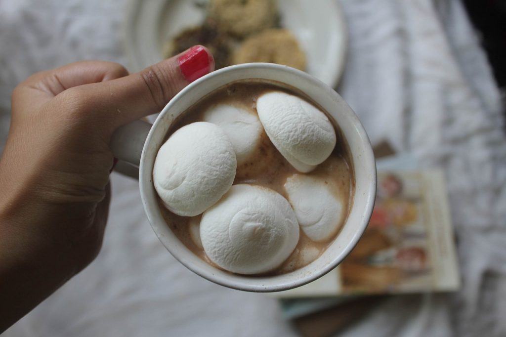 women holding a cup of hot chocolate with giant marshmallows in cup