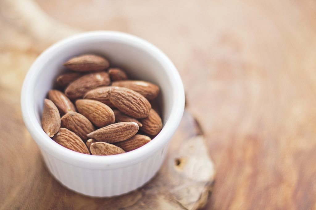 healthy snack; almonds in a white bowl on the table