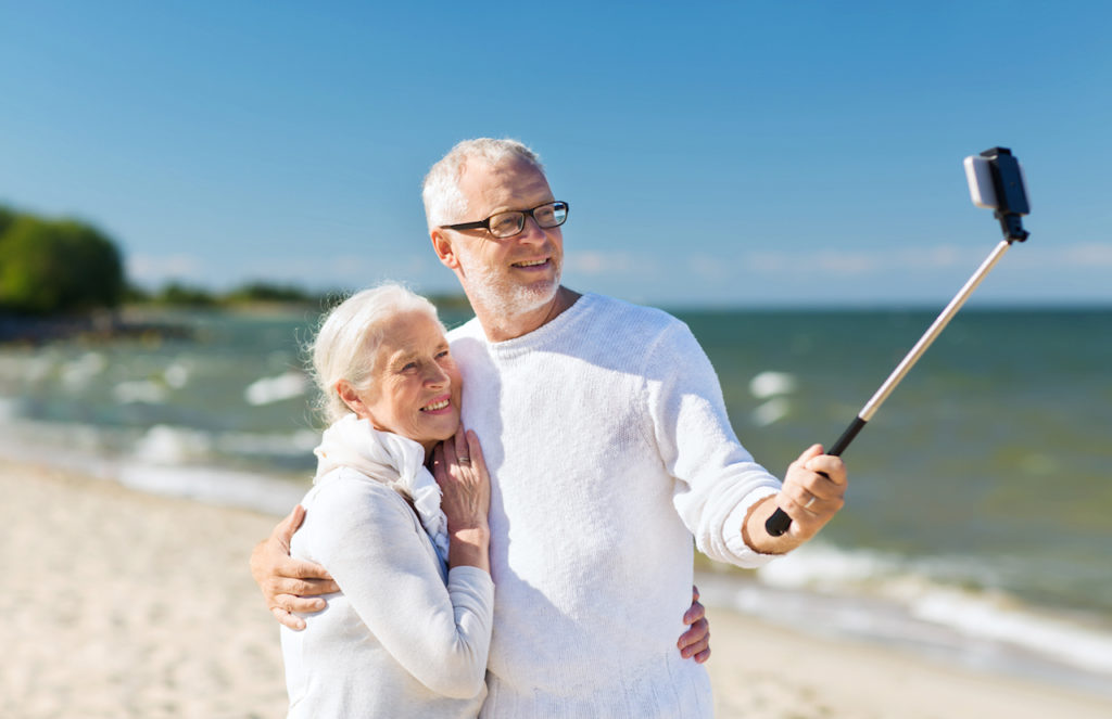 happy senior couple with smartphone selfie stick photographing and hugging on summer beach