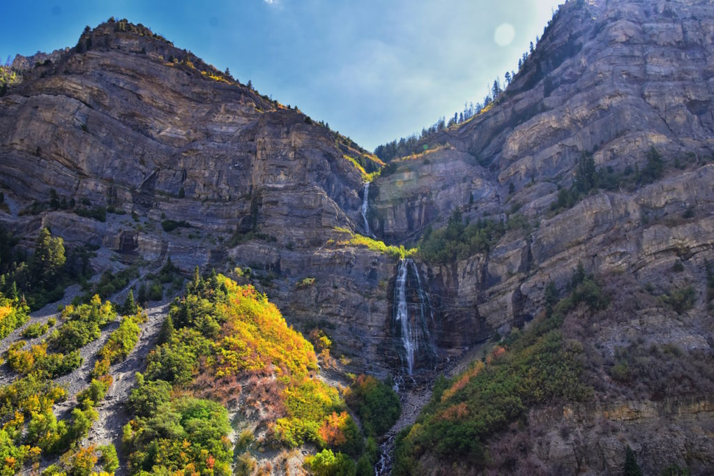 view of Bridal Veil Falls in Provo, Canyon with water falling and autumn leaves