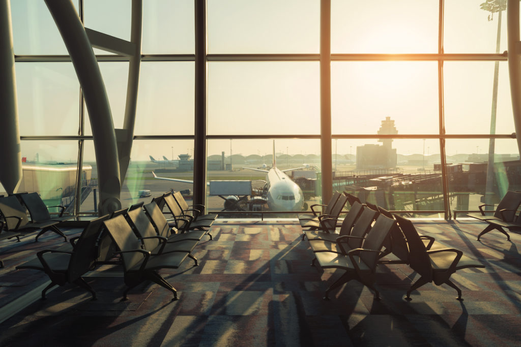 empty chairs inside of an airport, with view of an airplane through the window