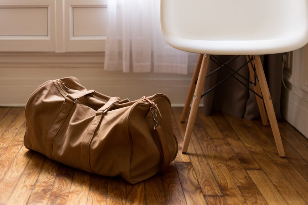 small brown duffel bag or suitcase on a wooden floor