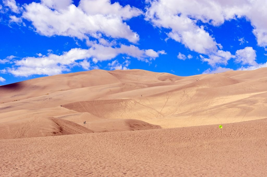 colorado sand dunes with a bright blue cloud filled sky