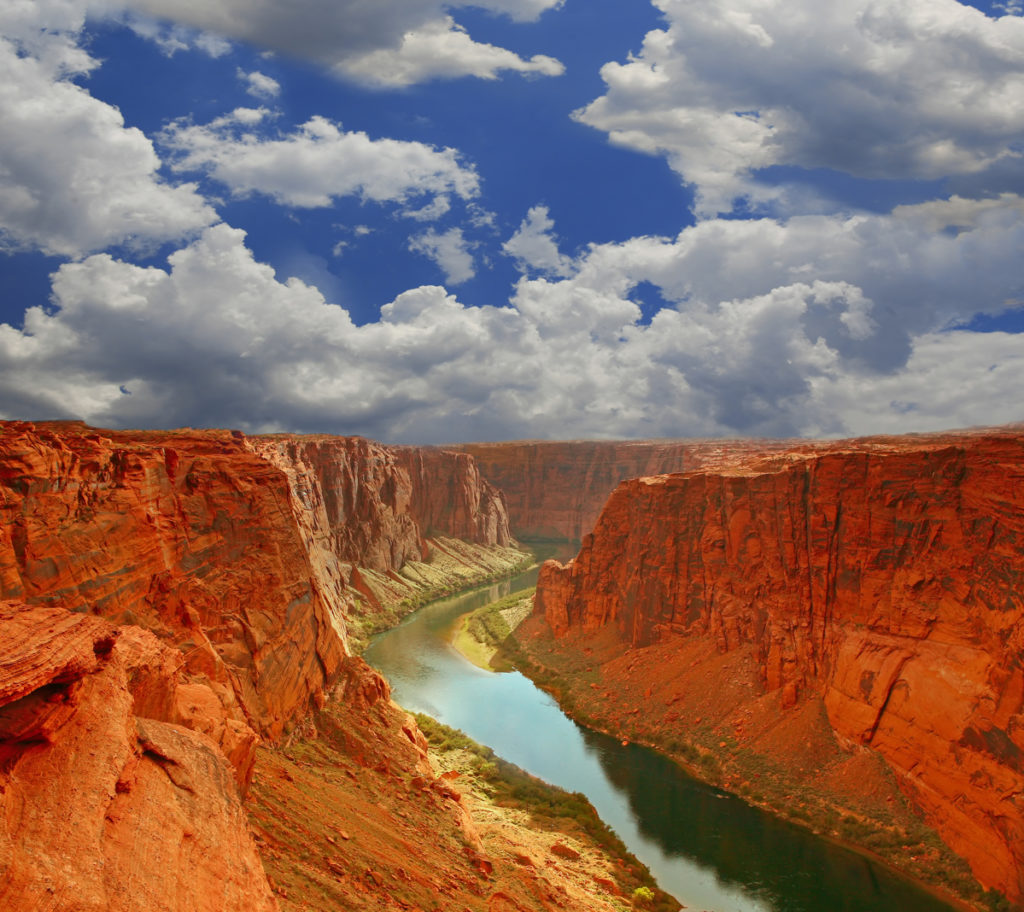 Blue skies and white clouds above the canyons and water inside Grand Canyon National Park