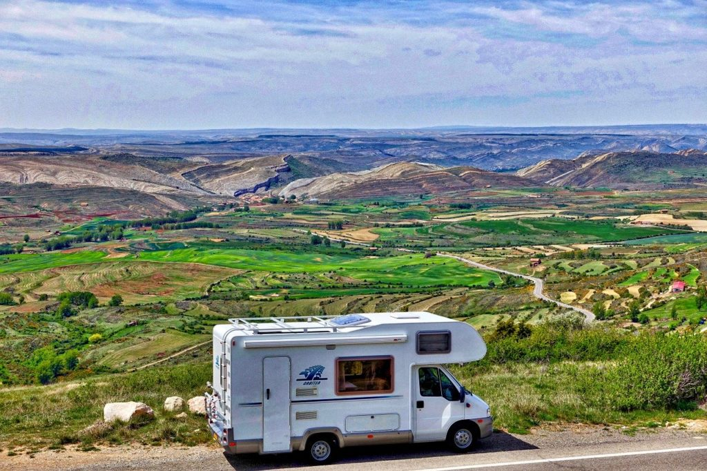 white rv with lots of green scenery in the background