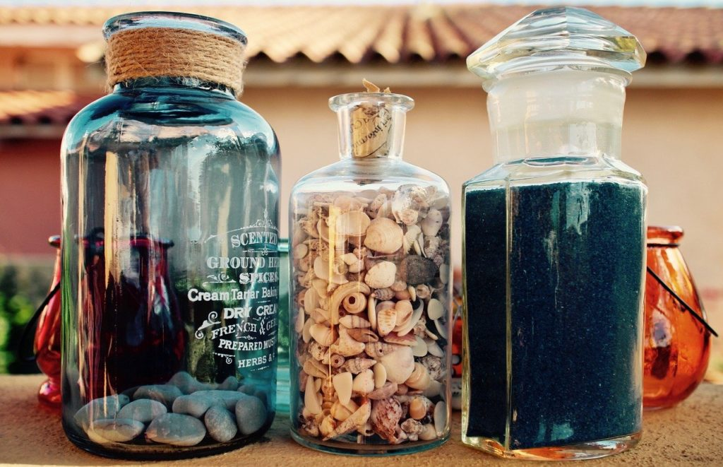 decorative jars on a table with seashells inside